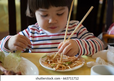 Young Japanese kid trying to use chopsticks.