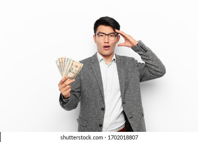 young japanese man looking happy, astonished and surprised, smiling and realizing amazing and incredible good news. money concept