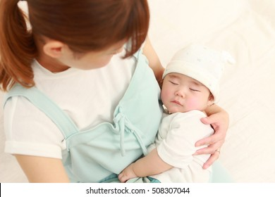 young Japanese mom and her sleeping baby