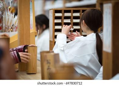 Young Japanese shrine maiden handing Omikuji over (Japanese fortune-telling paper strips) in Kamkura.