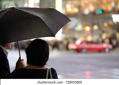 Young Japanese woman and an old Japanese man waiting together at the Shibuya crossing in Tokyo on a rainy night.