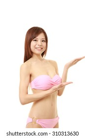 young Japanese woman in a pink bikini presenting and showing something
