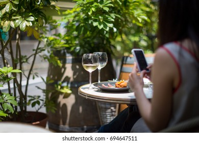 Young Japanese woman taking a picture of her lunch with a smart phone.