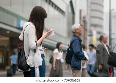 Young Japanese woman using her smartphone in Tokyo.