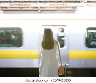 Young Japanese woman waiting for her train on the platform. The Japanese sign reads: Akihabara, the name of the station.