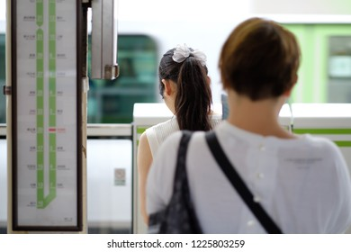 Young Japanese woman waiting for her train.