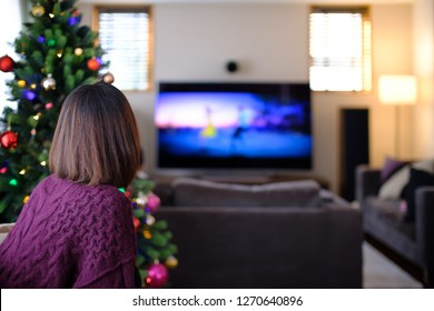 Young Japanese woman watching TV during Christmas Holidays.