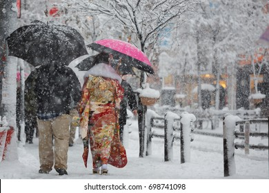 Young Japanese woman wearing a colorful kimono and walking outside in Tokyo during a snow storm.