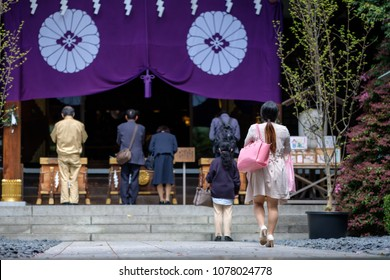 Young Japanese woman wearing a dress and carrying a pink handbag walking towards the altar of a shrine in Tokyo on a bright day in spring.