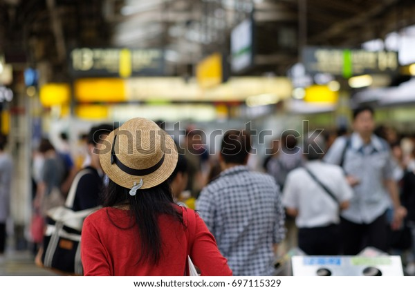 Young Japanese woman wearing a red cardigan and a straw hat in a railway station in Tokyo.