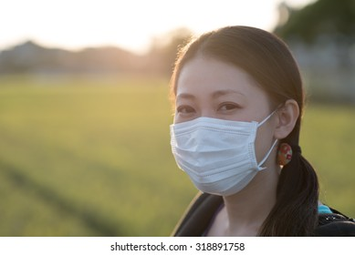 A young Japanese woman wearing a surgical mask outdoors in the countryside with a bright sunset behind her.