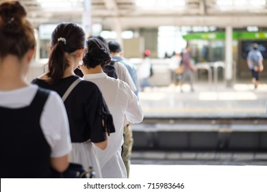 Young Japanese women waiting on a railway platform in Tokyo, Japan.