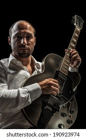 a young jazzer with a black acoustig guitar over black background