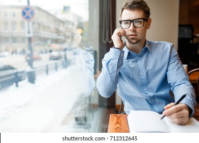 Young jobless man making appointment with employer on the phone