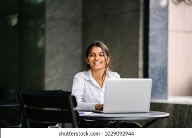 A young job-seeker applies for her job on her laptop computer. It is a portrait of her (Indian Asian woman) sitting at a table as she smiles and fills in her application.