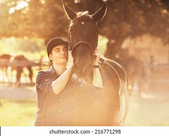 Young jockey preparing his horse for a ride
