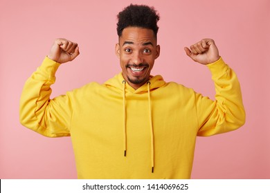 """Young joyful african american man in yellow hoodie, raising his fists up, say """"i'm cool' and stands over pink background and smiling broadly."""