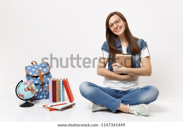 Young joyful beautiful woman student in glasses denim clothes holding book sitting near globe, backpack, school books isolated on white background. Education in high school university college concept