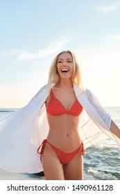 Young joyful blond woman in red swimsuit and white shirt happily standing on beach with sea on background