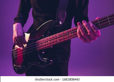 Young and joyful caucasian musician playing guitar on gradient purple studio background in neon light. Concept of music, hobby, festival. Colorful portrait of modern artist. Attented and inspired.