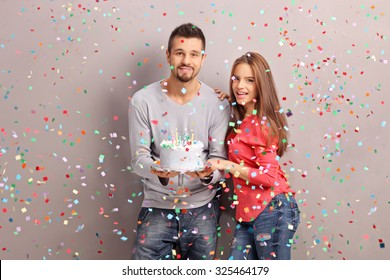 Young joyful couple holding a birthday cake with a lot of confetti streamers flying around them