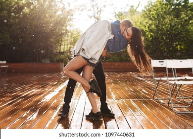 Young joyful couple hugging while dancing under rain in park. Beautiful couple spending time together
