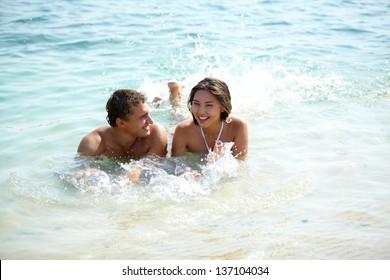 Young joyful couple lying in water and splashing playfully