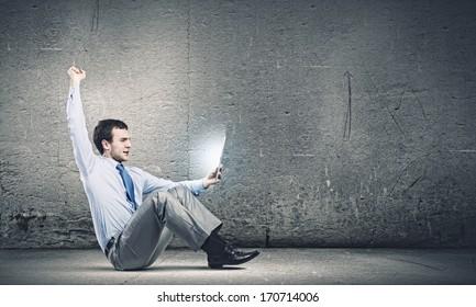 Young joyful handsome businessman using tablet pc