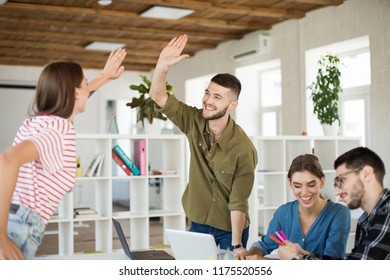 Young joyful man in shirt happily giving  high five to colleague spending time at work. Group of creative guys working together in modern office