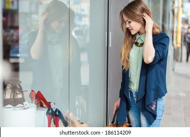 Young joyful woman looking at the shop window