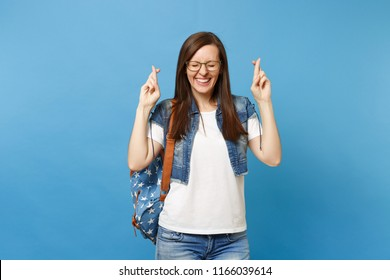 Young joyful woman student in glasses with backpack waiting for special moment keeping fingers crossed and eyes closed isolated on blue background. Education in high school university college concept