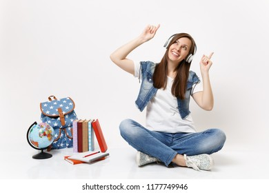 Young joyful woman student with headphones listening music pointing index fingers up sitting near globe backpack school books isolated on white background. Education in high school university college