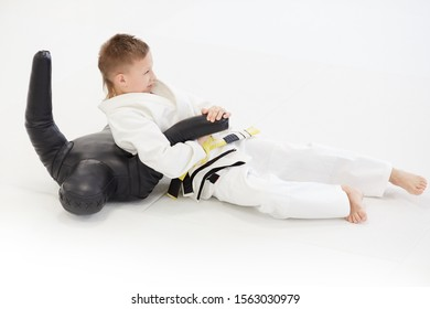 Young judoist in white kimono lying on the floor and practicing technique in karate on mannequin