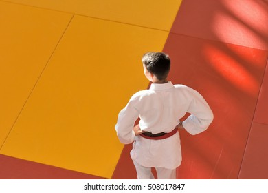 Young judoka gets ready to enter on a tatami during a competition/judoka