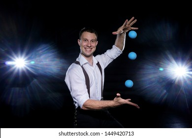 young juggler in white shirt and pants in suspenders juggles during a concert on stage with a black background and spotlights