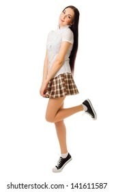 Young jumping girl in plaid skirt isolated