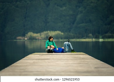 Young just married couple is sitting on pier by the volcanic lake on Azores islands. Low angle view, front view, soft focus. Mountain on background.