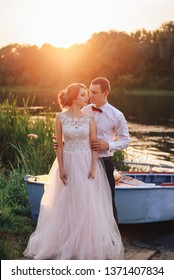 Young just married couple in wedding gown and suit standing near the boat at the seaside looking aside. Groom embracing his beautiful bride. Wedding day concept. Copy-space. Outdoor shot