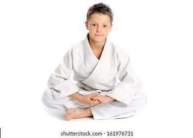 Young karate boy sitting in lotus pose