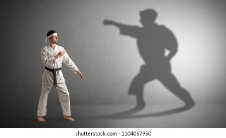 Young karate man confronting with his own shadow