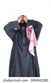 Young khaleeji man covering his face with hands looking up exasperated, isolated on a white background.