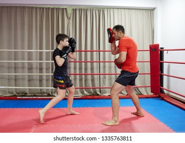 Young kickbox fighter hitting mitts with his coach