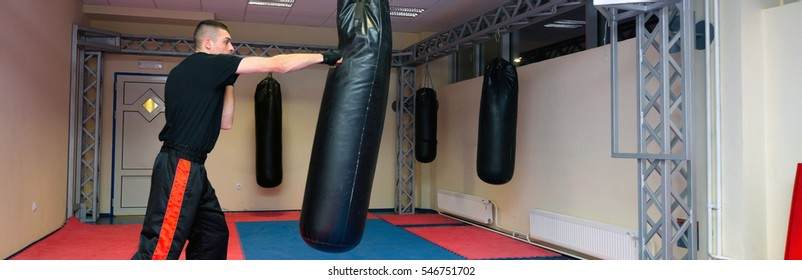 Young kickboxer kicking and punching punching bag in sport gym.