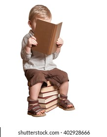 Young Kid boy reading a book on the stack of books. 2 years old Child isolated on white