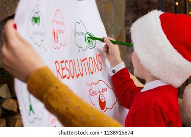 Young kid child boy in red santa hat making his resolution goals for 2019 New Year for his family: mother woman and father male man during winter holidays. Merry Christmas and Happy New Year concept.