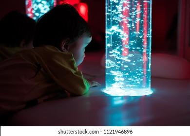 Young kid exploring a multi sensory space - snoezelen concept