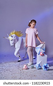 Young kid girl in elegance dress pink. Concept winter, eve, Christmas, new year. Fashion lady teenage poses for children's clothing catalog. White big unicorn origami near. Studio purple background.