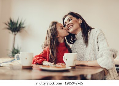 Young kid girl kissing mum on cheek and smiling. She sitting in cozy cafe with light interior and spending time with happy mum