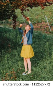 Young kid girl playing with a tree in beautiful garden at sunset light