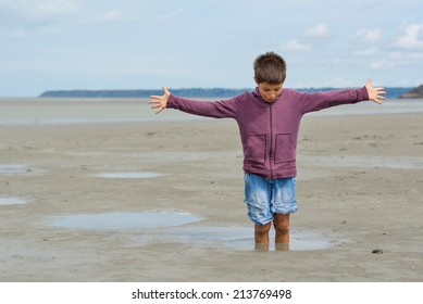 Young kid having fun with quicksand on the beach in front of Mont Saint Michel ancient village. Normandy, France.